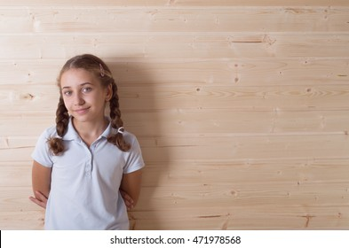 happy child little girl laughing at empty wooden wall