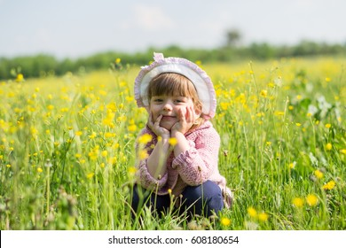 Happy child little girl played on the nature among the flowers