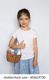 Happy child, little girl showing thumbs up gesture in a white T-shirt isolated on white background. Space for Your Text. Ok sign. cute girl with eggs for the Easter holiday