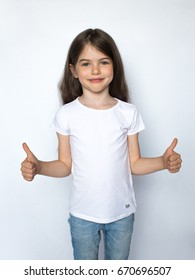 Happy child, little girl showing thumbs up gesture in a white T-shirt isolated on white background. Space for Your Text. Ok sign