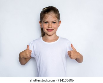 Happy child, little girl showing thumbs up gesture in a white T-shirt isolated on white background. Space for Your Text. Ok sign. Concept of success.