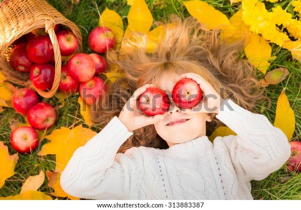 Gelukkig kind liggend op herfstbladeren. Grappig kind buiten in de herfst park