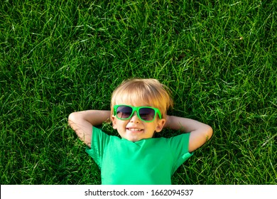 Happy child lying on green grass. Smiling boy having fun outdoor in spring garden