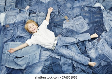 Happy Child Lying on Jeans Clothes Background. Denim Fashion