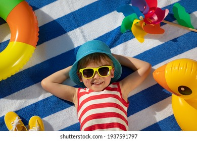Happy child lying on striped towel outdoor. Top view portrait of kid. Funny baby smiling. Summer vacation concept