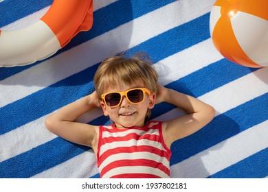Niño feliz tumbado en una toalla rayada al aire libre. Retrato de vista superior de niño. Un bebé gracioso sonriendo. Concepto de vacaciones de verano