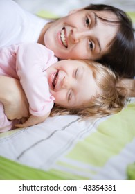 Happy child with mom - shallow DOF, focus on little girl's eyes