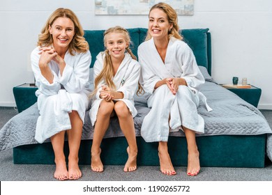 happy child with mother and grandmother in bathrobes sitting on bed at home and looking at camera