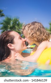 Happy child with mother playing in swimming pool. Summer vacations concept