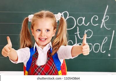 Happy child near blackboard show thumb up.