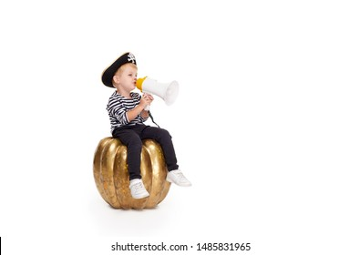 Happy child on Halloween. Funny little boy in carnival costumes of pirates sitting on a big orange pumpkin and speaking into a loudspeaker shout on white background. trick or treat. Space for text