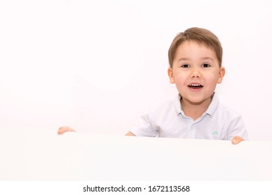 Happy child on a light background holding a light background at the bottom