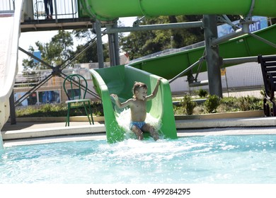 Happy child on water slide at aquapark in summer
