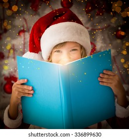 Happy child opening magic Christmas book. Xmas holiday concept