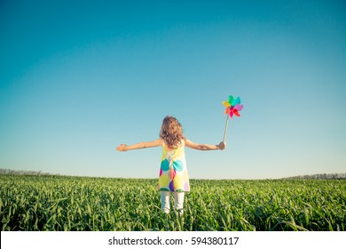Happy child outdoors against blue sky background. Kid having fun in green spring field. Freedom and imagination concept