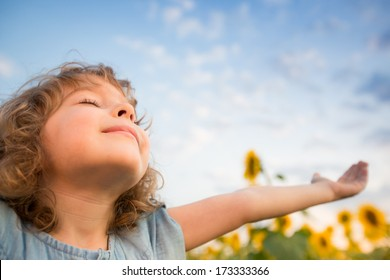 Happy child outdoors in spring sunflower field