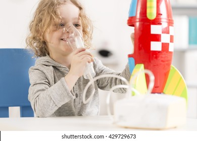Happy child with oxygen mask playing with toy racket