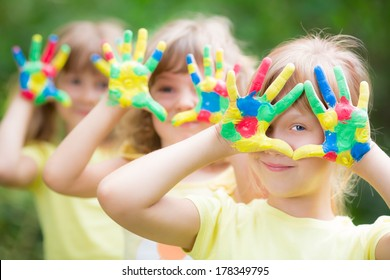 Happy child with painted hands against green spring background