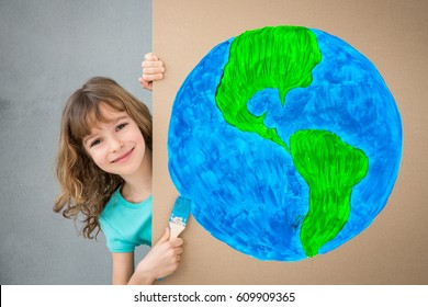 Happy child painting the cardboard with blue color. Kid having fun at home. Spring renovation and Earth day holiday concept