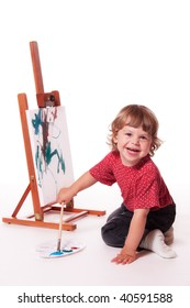 Happy child painting on easel