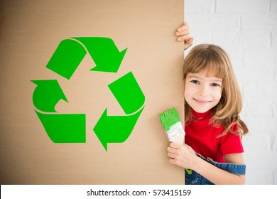Happy child painting recycle symbol on cardboard. Funny girl playing at home. Spring renovation and design concept