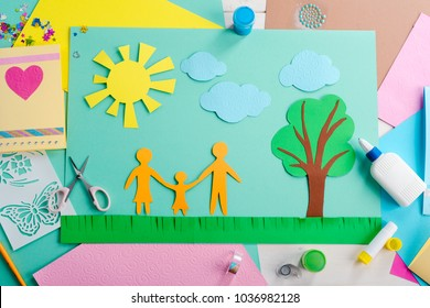 Happy child and parents. Top view on a picture made of cutout paper shapes such as people, sun, clouds, tree and grass. Kid's idea for international family day.
