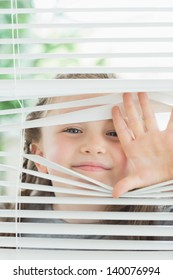 Happy child peeking through window blinds