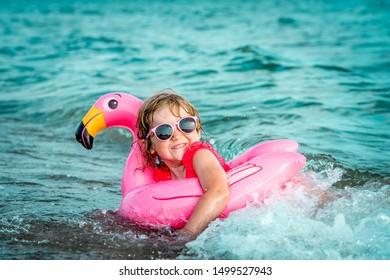 Happy child in pink glasses and with pink flamingo playing in the sea waves. Excited and laughing kid having fun on summer vacation with family.