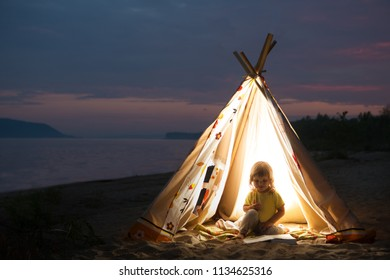 happy child  play in a tent in the evening on the river bank