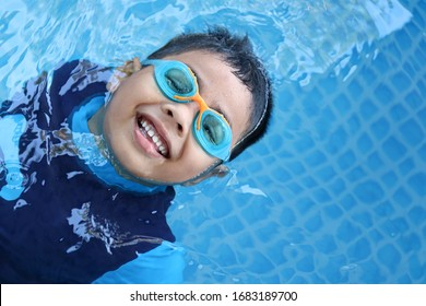 Happy child playing in blue colour swimming pool. Boy with swimming goggles. Kid practice water sport. Summer vacation concept.