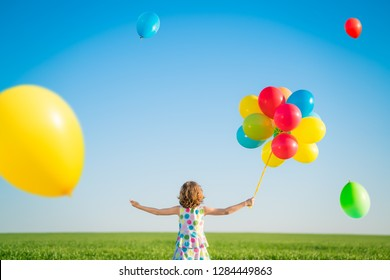 Happy child playing with bright multicolor balloons outdoor. Kid having fun in green spring field against blue sky background. Healthy and active lifestyle concept. Rear view