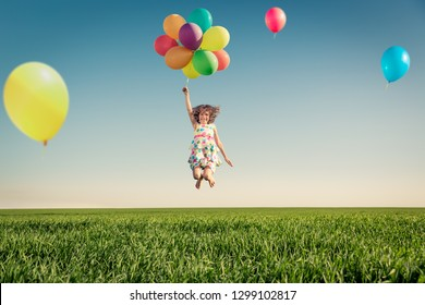 Happy child playing with bright multicolor balloons outdoor. Kid having fun in green spring field against blue sky background. Healthy and active lifestyle concept