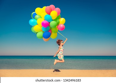 Happy child playing with bright multicolor balloons on summer vacation. Kid having fun on the beach against blue sea and sky background. Healthy and active lifestyle concept