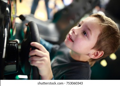 Happy child playing in car simulator at indoor playground