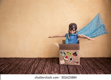 Happy child playing in cardboard box. Kid having fun at home