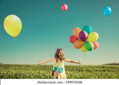 Happy child playing with colorful toy balloons outdoors. Kid having fun in green spring field against blue sky background. Freedom and imagination concept