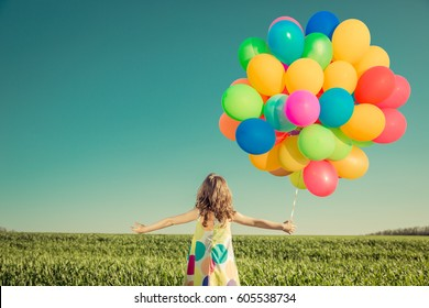 Happy child playing with colorful toy balloons outdoors. Little girl having fun in green spring field against blue sky background. Freedom and imagination concept