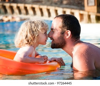 Happy child playing with father in blue water of swimming pool on a tropical resort at the sea. Summer vacations concept