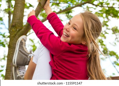 Happy child playing in the garden climbing on the tree