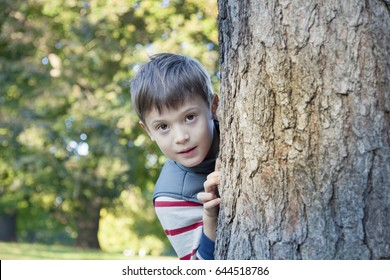 Happy child playing hide and seek in nature and looking out of wood. Happy childhood. Concept of happy holiday.