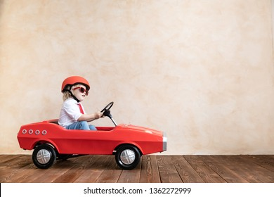 Happy child playing at home. Funny kid driving toy car indoor. Success and win concept