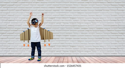 Happy child playing at home. Kid pilot with toy jetpack. Children In Pilot Costumes Dreaming Of Piloting The Plane. Success, leader and winner concept