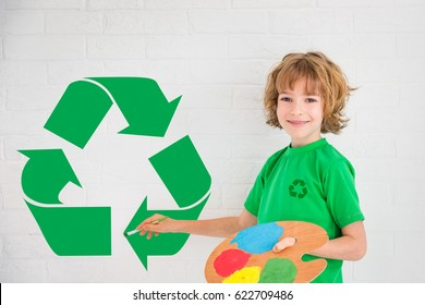 Happy child playing at home. Kid drawing green recycle sign on the wall.. Spring renovation and Earth day concept