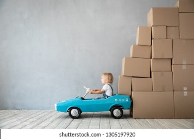 Happy child playing into new home. Kid driving toy car. Moving day concept
