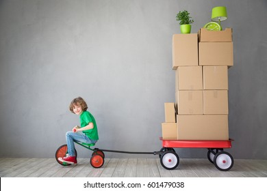 Happy child playing into new home. Kid having fun indoor. Courier riding tricycle. Moving house day and express delivery concept
