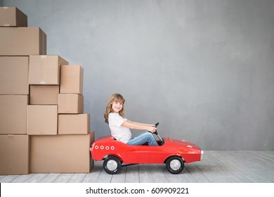 Happy child playing into new home. Kid having fun indoor. Moving house day and express delivery concept