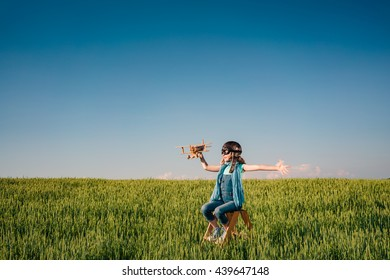 Happy child playing. Kid with toy airplane. Child having fun outdoors. Kid in summer field. Travel and vacation concept. Imagination and freedom concept