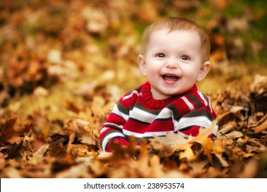 Happy child playing in a leaf pile during fall or winter
