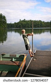 A happy child is playing on a dock by a fishing row boat in a Northern Wisconsin small lake in the woods.