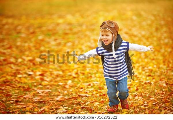 glückliches Kind, das Pilotenaviator und Träume im Herbst im Freien spielt
